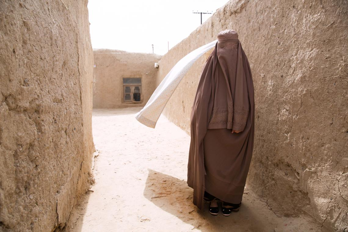 A woman in a burka walks down an alley, Afghanistan