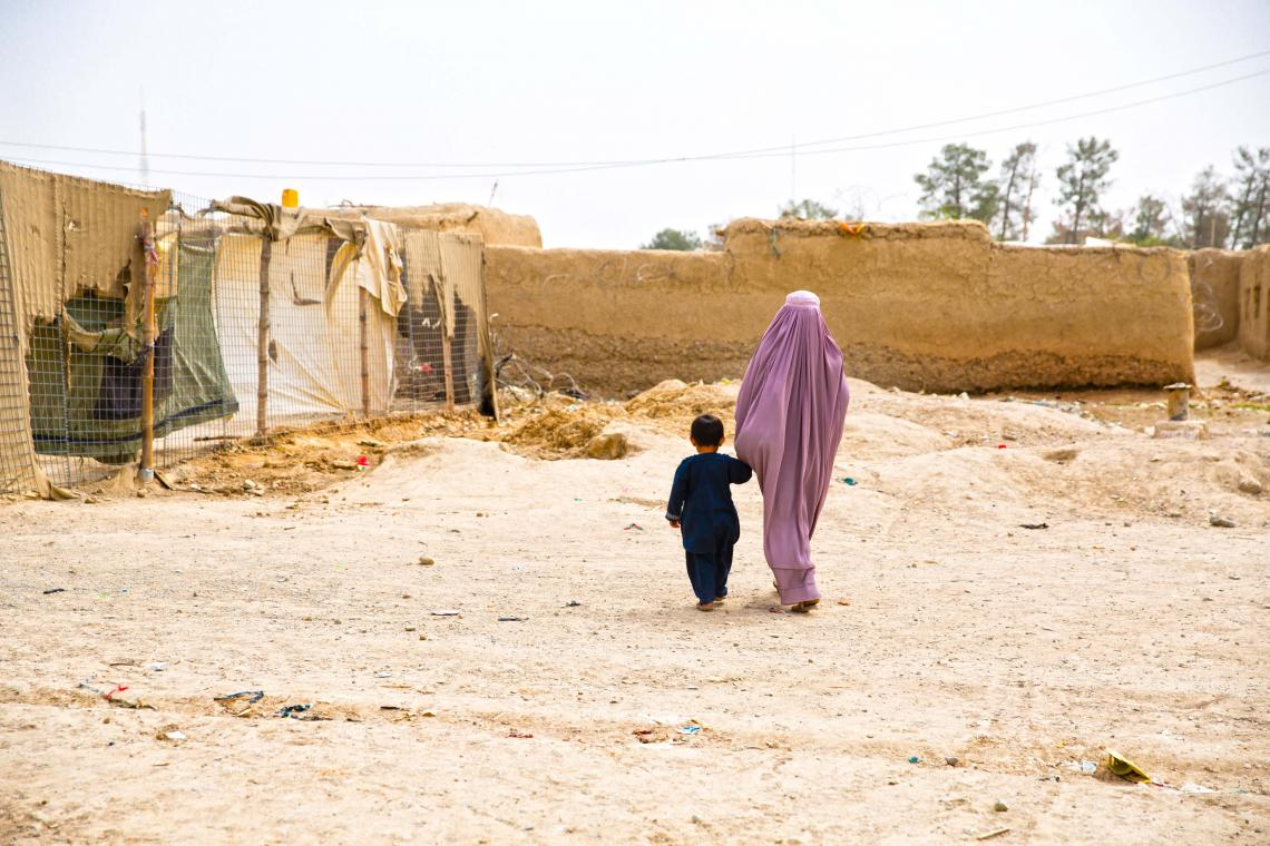 A woman walks holding hands with a boy, Afghanistan