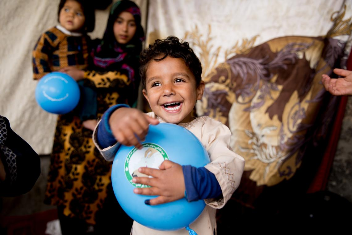 A boy laughs while holding a balloon, Afghanistan