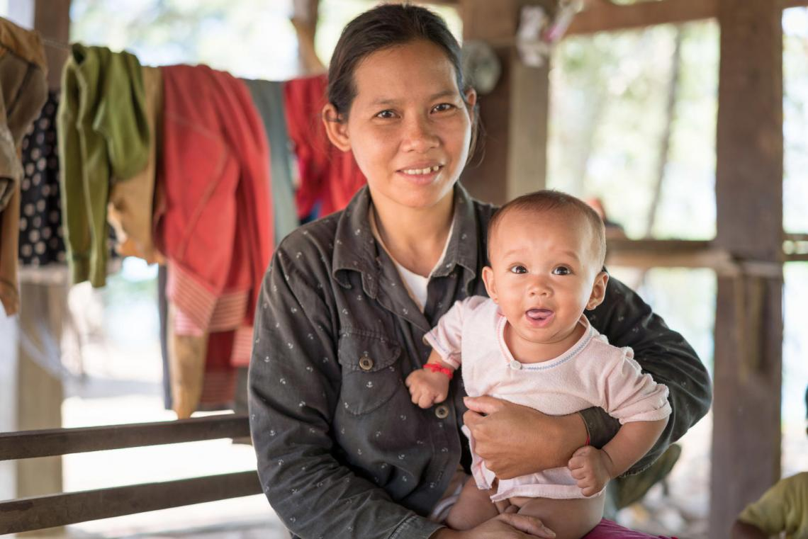 A mother in Cambodia holds her smiling infant.