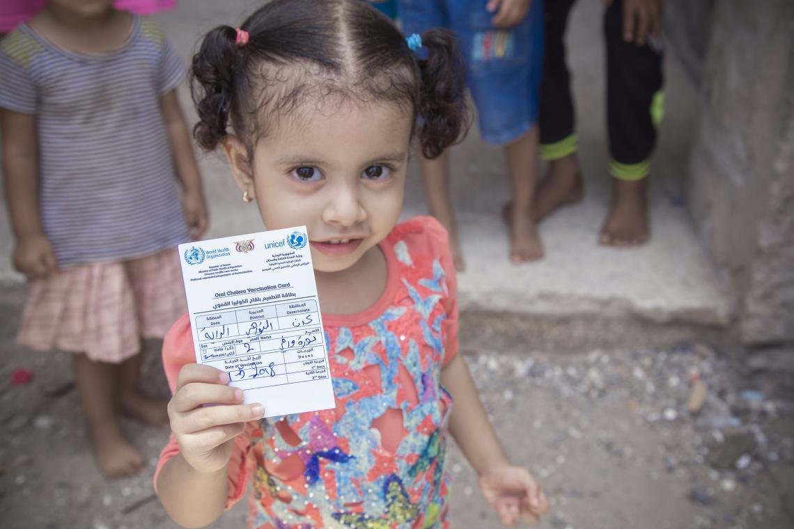 A girl holds up her vaccination card in Yemen