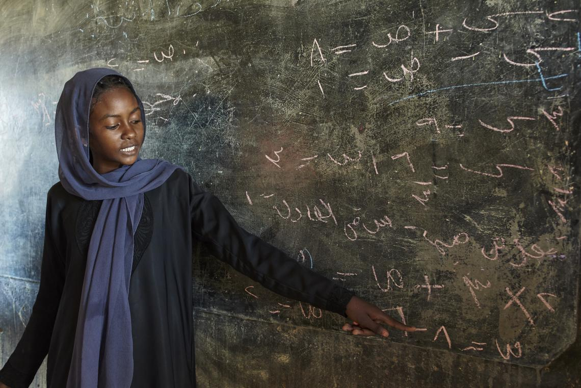 En ung pige står foran et tavle mod sin klasse for at forklare en matematisk ligning.