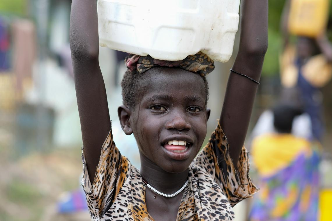 A girl heads home with the jerrycan of clean water