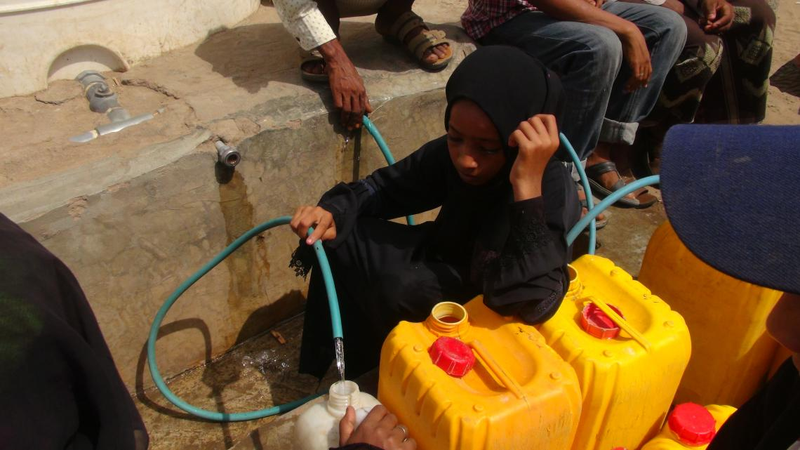 A girl fills a jerrycan with water in Hodeidah, Yemen