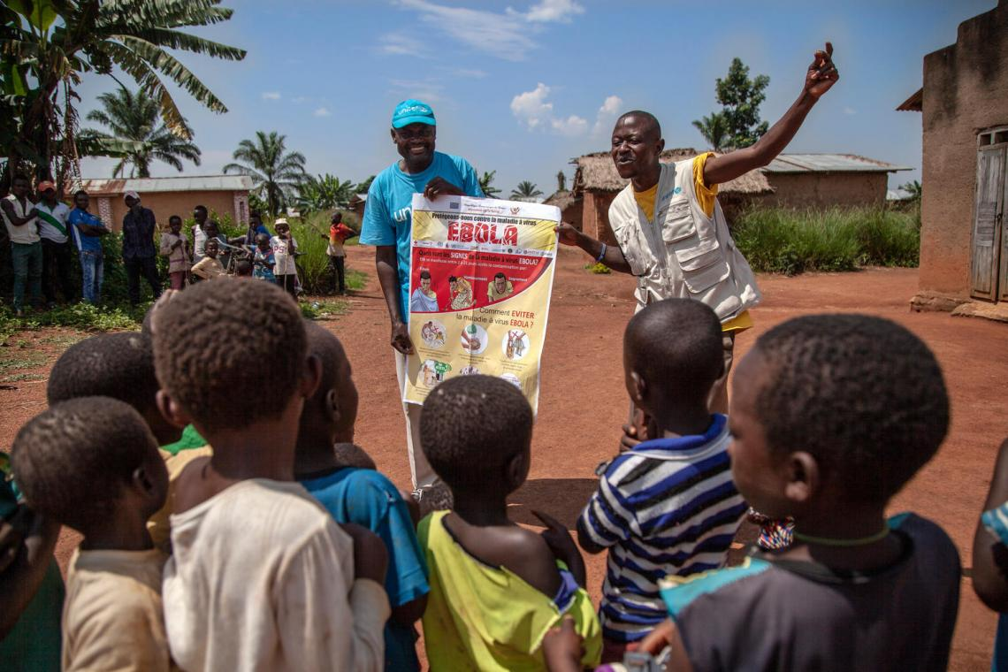 Two UNICEF workers speak about the Ebola virsu to a group of children in the Democratic Republic of Congo.