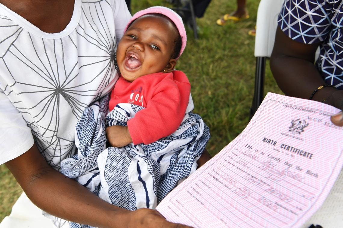 A baby smiles next to her birth certificate, Ghana