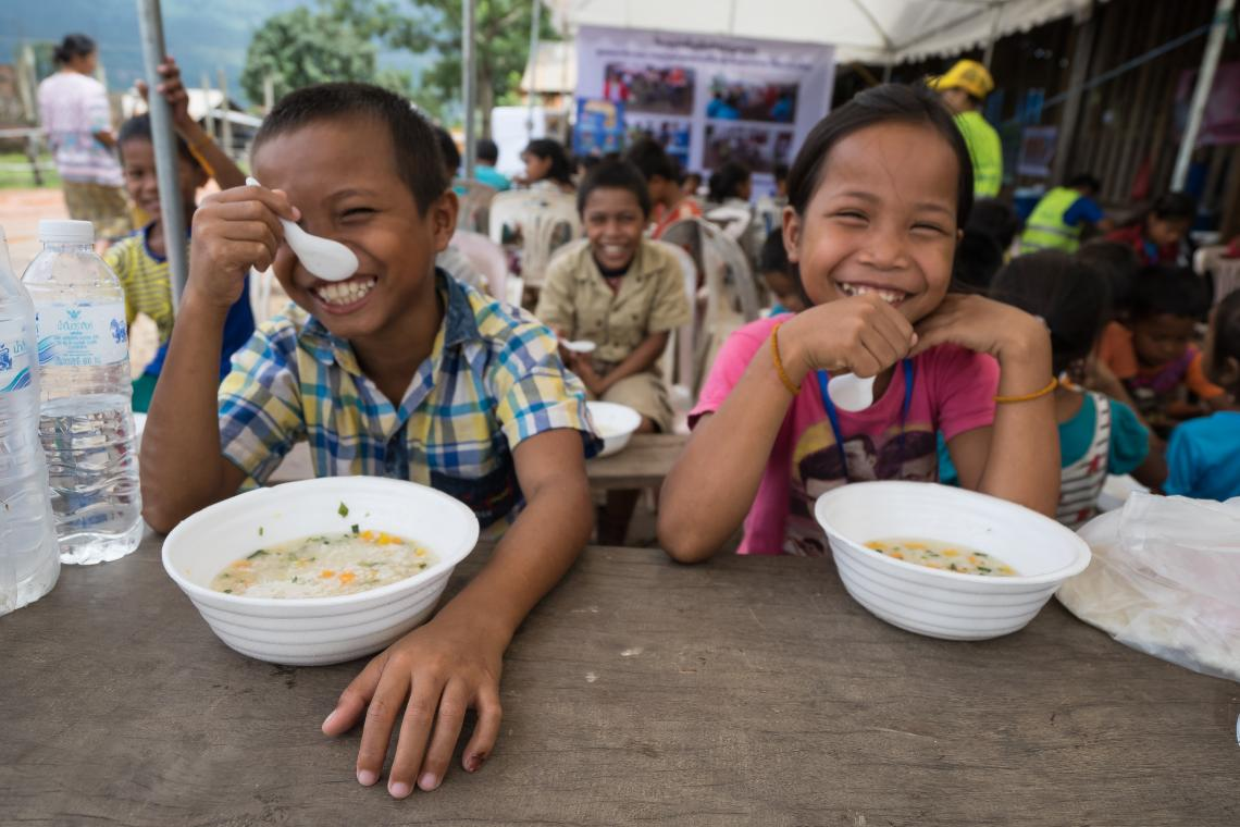 Two children smile while eating food in Oudomxay camp, Attapeu, Lao PDR.