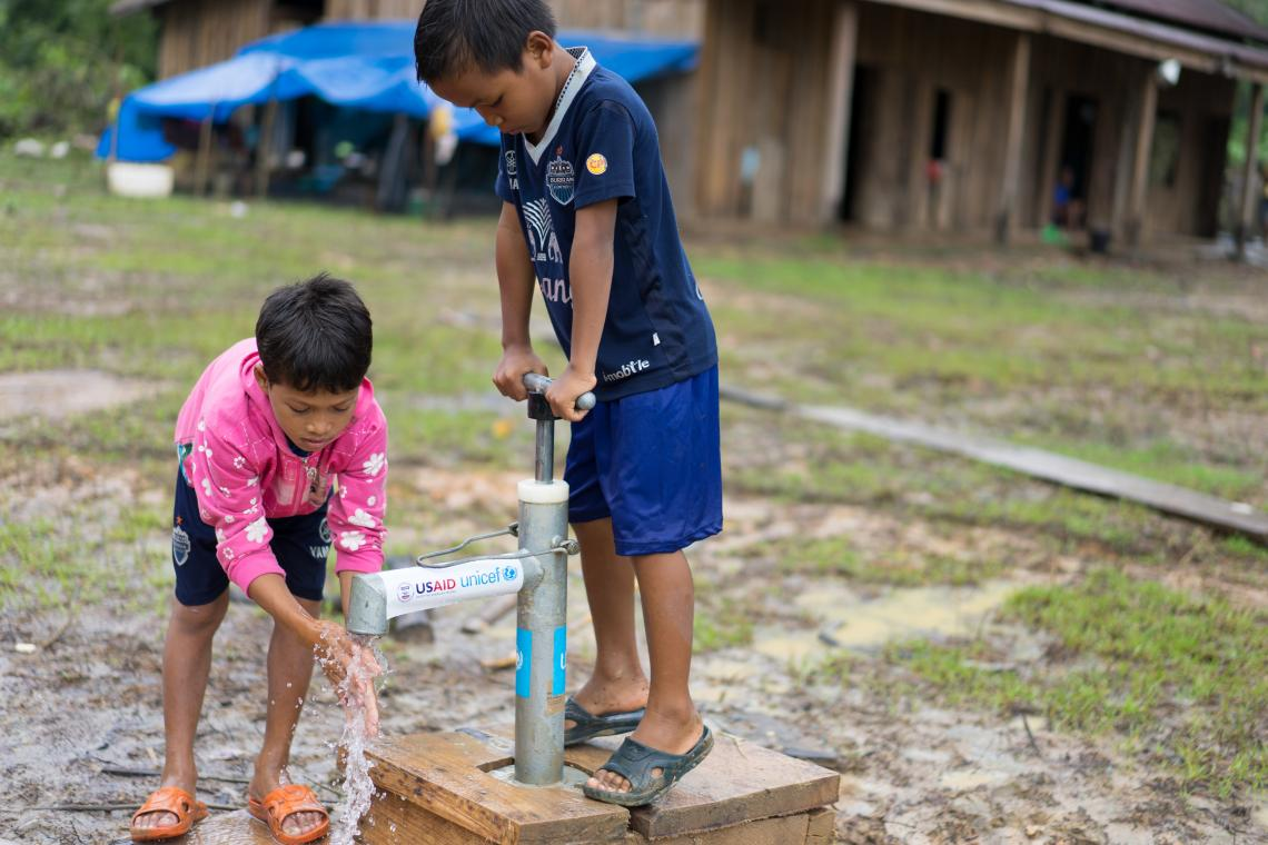 Two boys use a tap in Ban Bok camp, Attapeu, Lao PDR.
