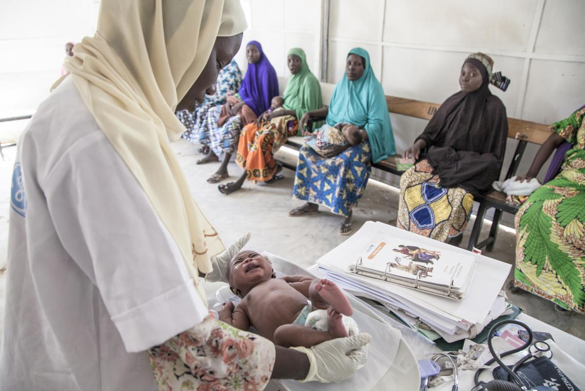 A midwife weights a newborn at a health centre, Nigeria
