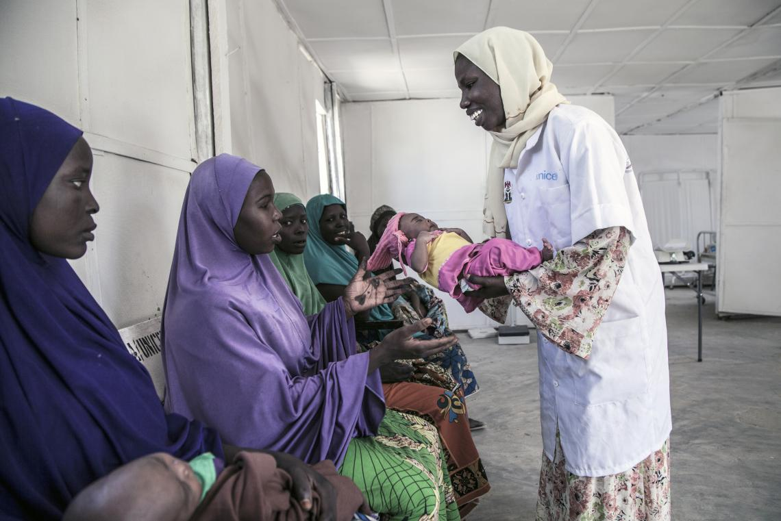A midwife hands a newborn to her mother, Nigeria