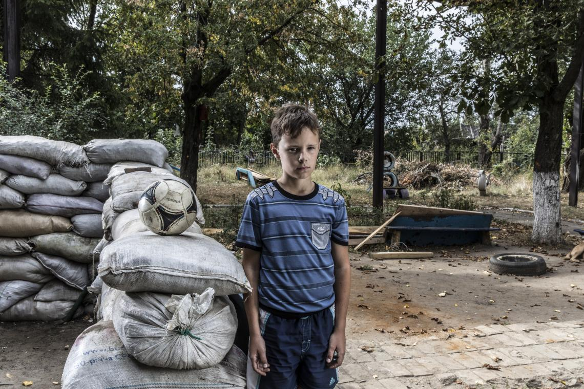 A boy stands next to a checkpoint in Ukraine.