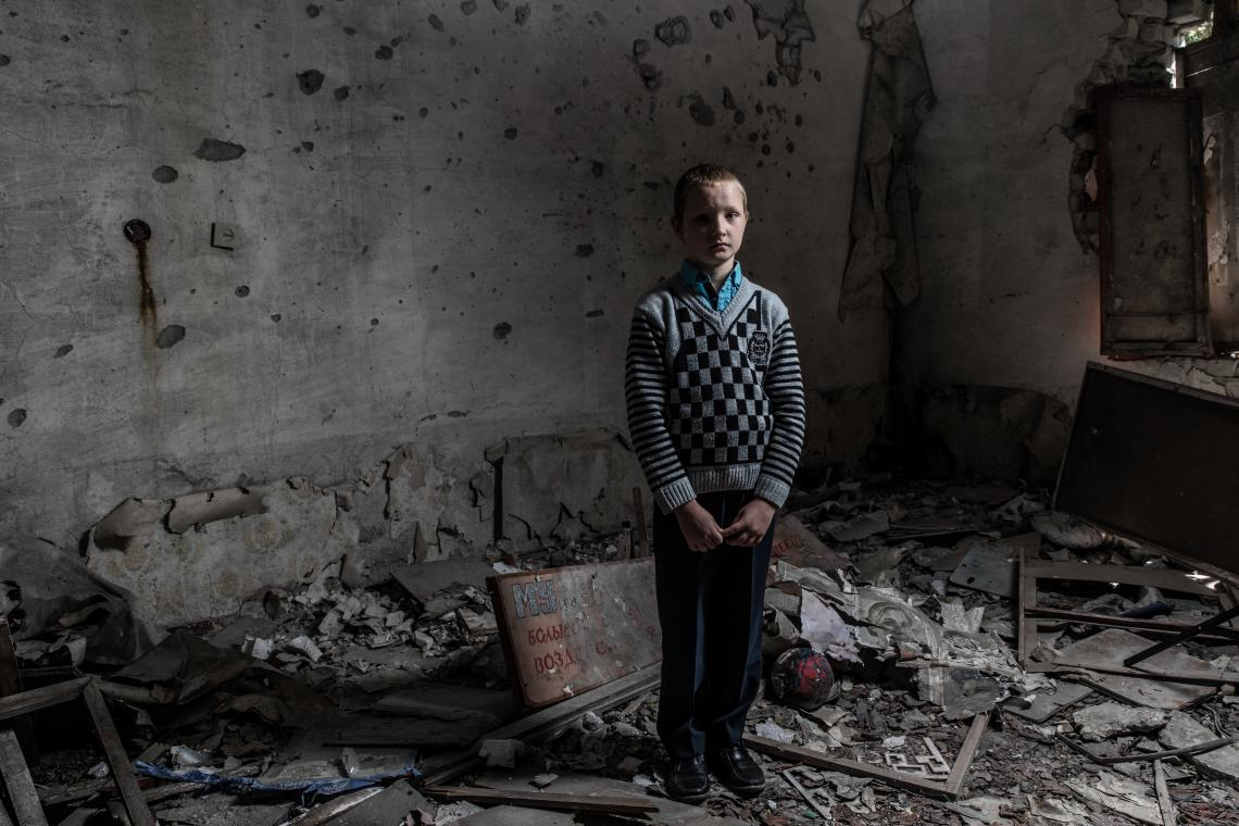 Yura Khromchenko, 9, stands in the classroom that took a direct hit from a shell