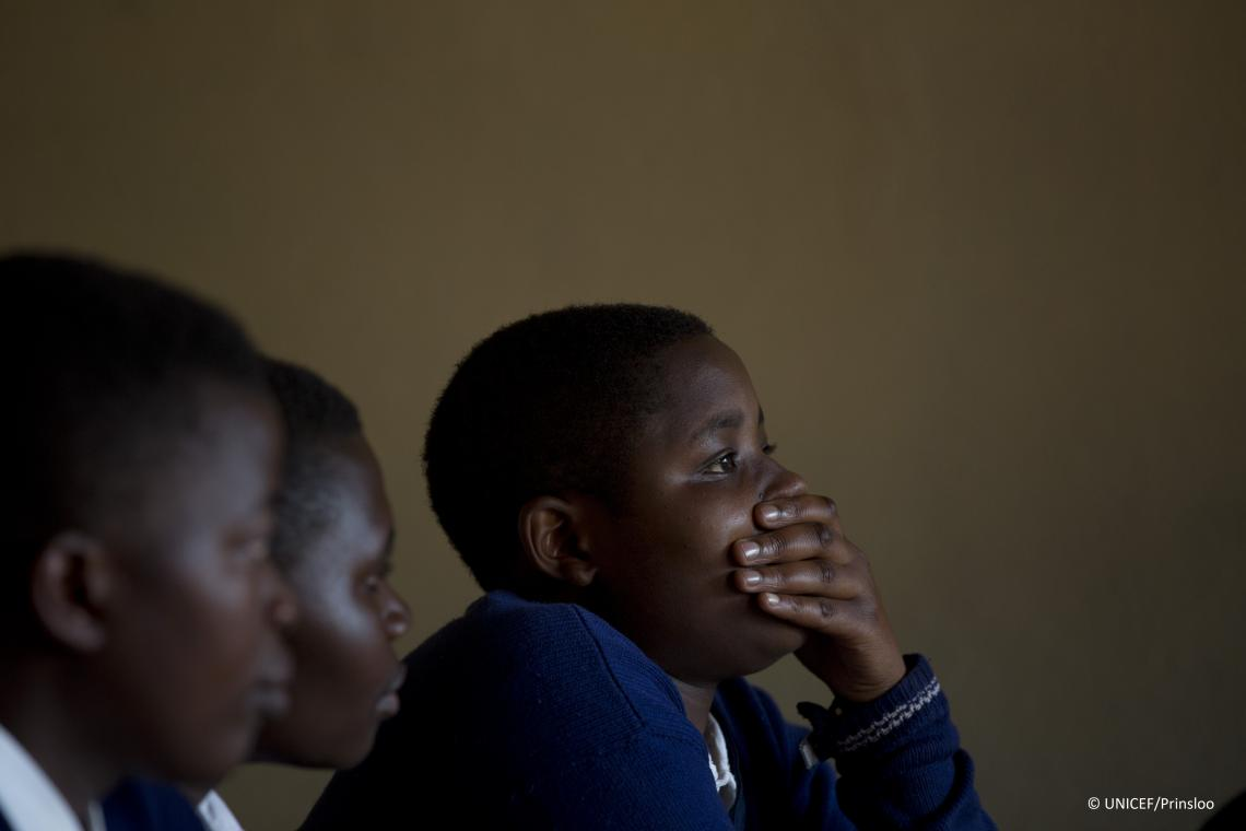 A girl puts her hand over her mouth, Rwanda