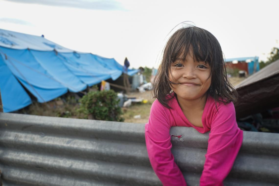 A girl smiles in front of a tent, Indonesia