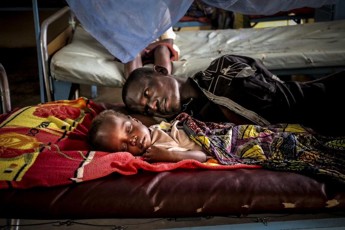 Central African Republic. A man lays with his child at a clinic.