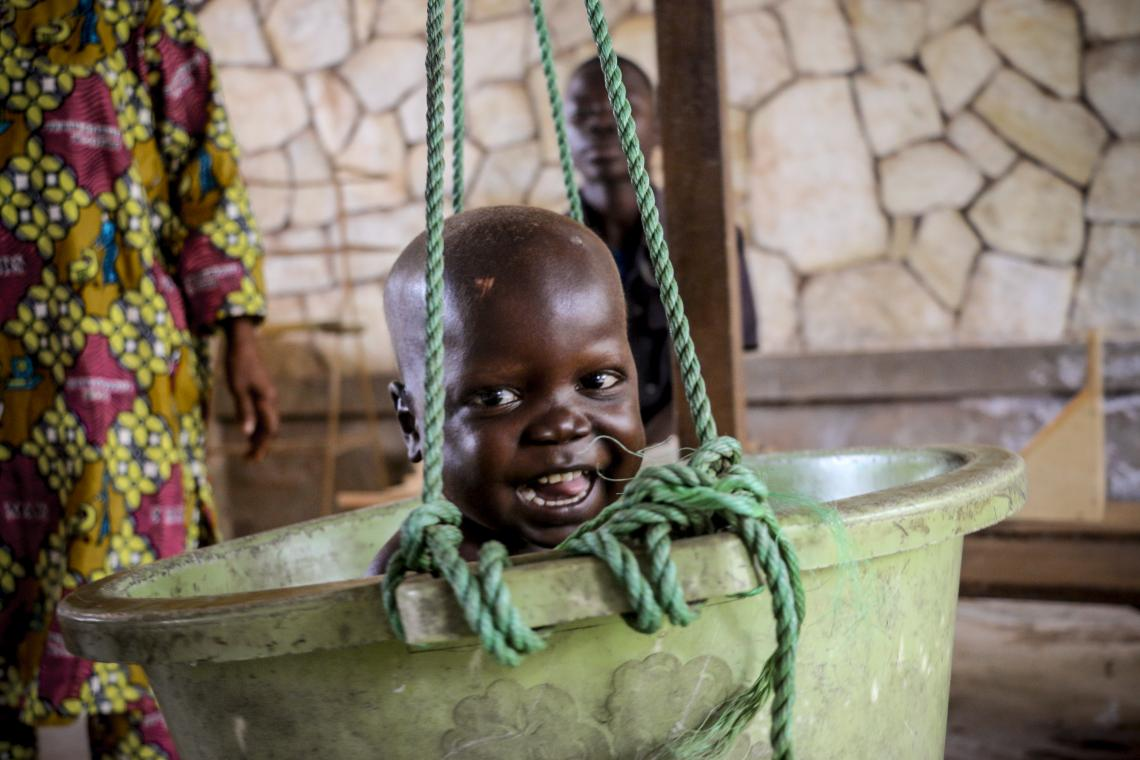 A boy is weighed in a bucket, Central African Republic