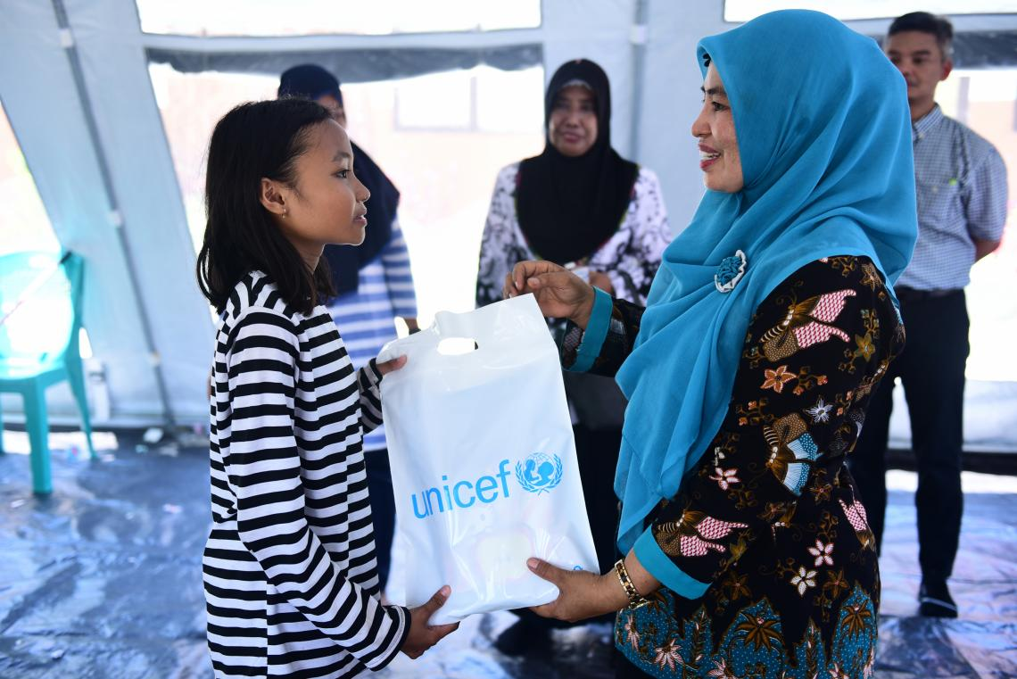Indonesia earthquake and tsunami. A displaced student receives a bag of school equipment.