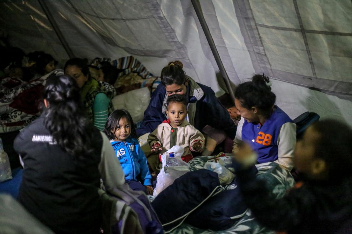Migrant children and mothers gather at a rest tent in Ecuador.