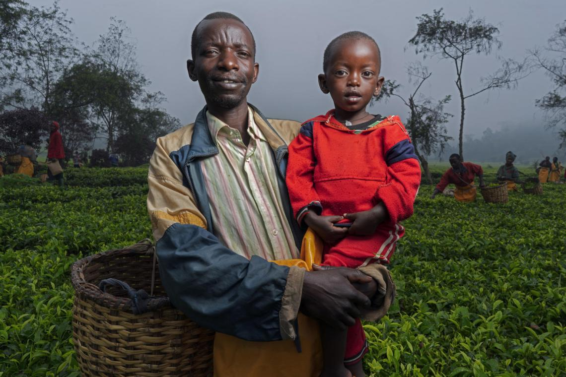 Christophe, 42, holds his son Kevin, 2, at the tea factory and plantation in Rwanda where he is employed as a tea plucker.