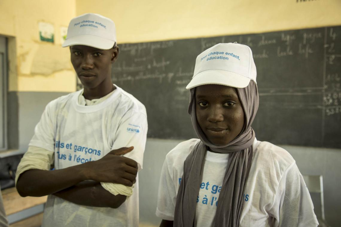 A boy and girl stand in a classroom, Mali