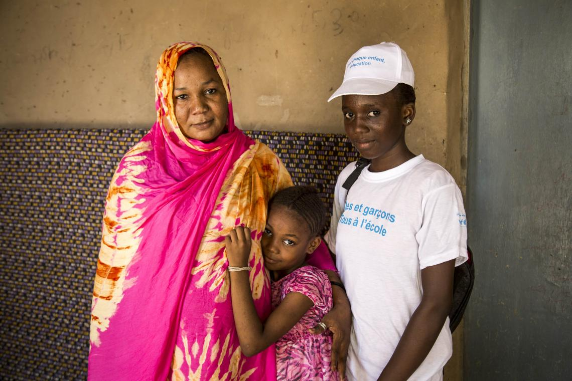 A teenage girl stands with a mother and daughter, Mali