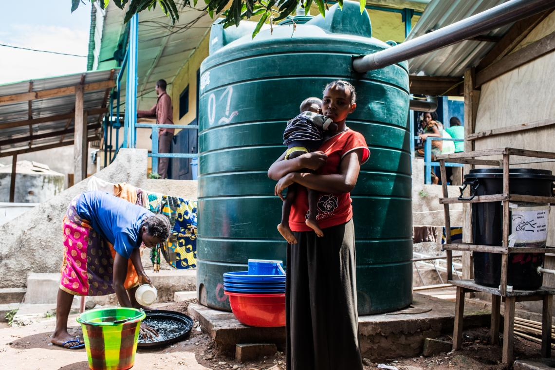 A woman holds a child in front of a water tank