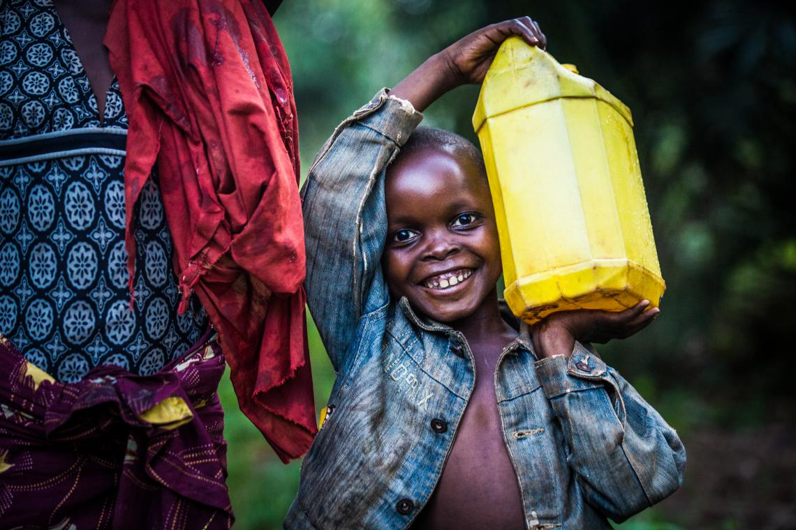 A young girl carries a bucket full of water from a water station