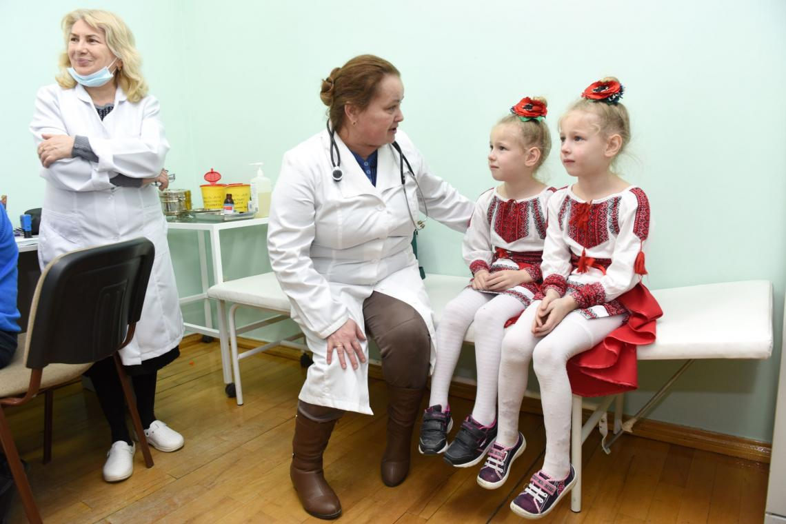 Ukraine. Two sisters wait with a doctor before their mumps, measles and rubella (MMR) vaccination in the Lviv region of western Ukraine.