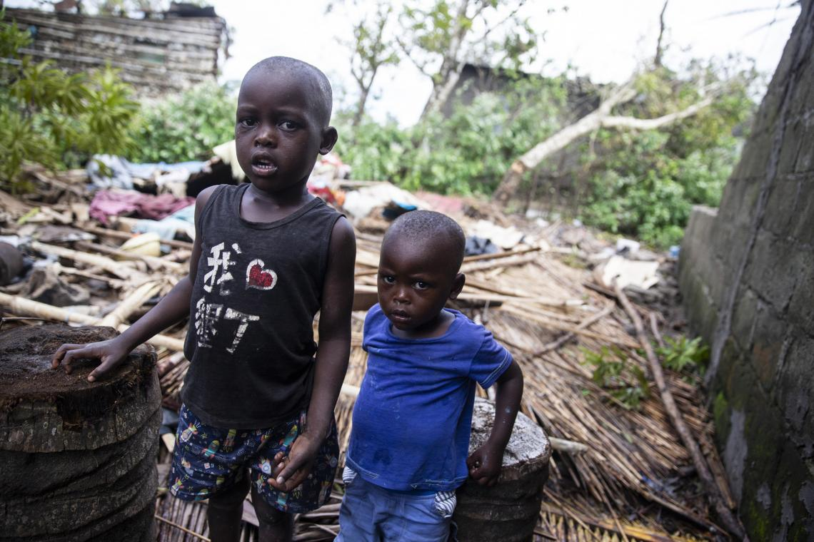 Mozambique. Two brothers stand by their destroyed home.