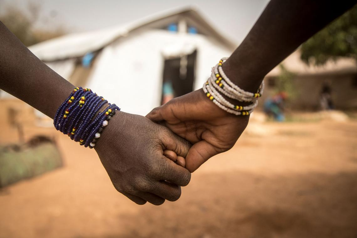 Mali. hold hands at a newly created displacement site in Sevare.