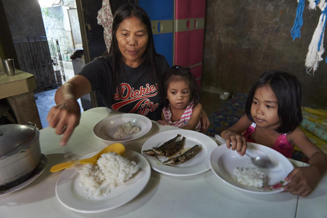 A woman sits with two children at a table, Philippines