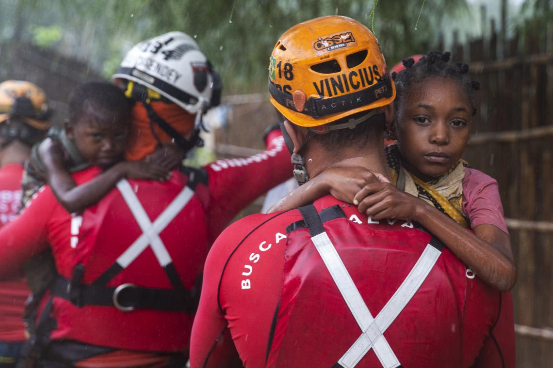 Mozambique. Brazilian Military Firefighters carry children rescued during heavy flooding in the Pemba region of Mozambique in April.