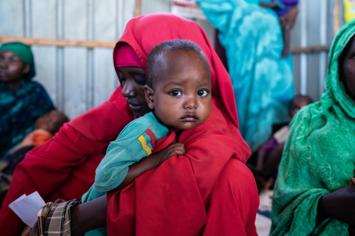 A woman in red holds her son over her shoulder in a health centre.