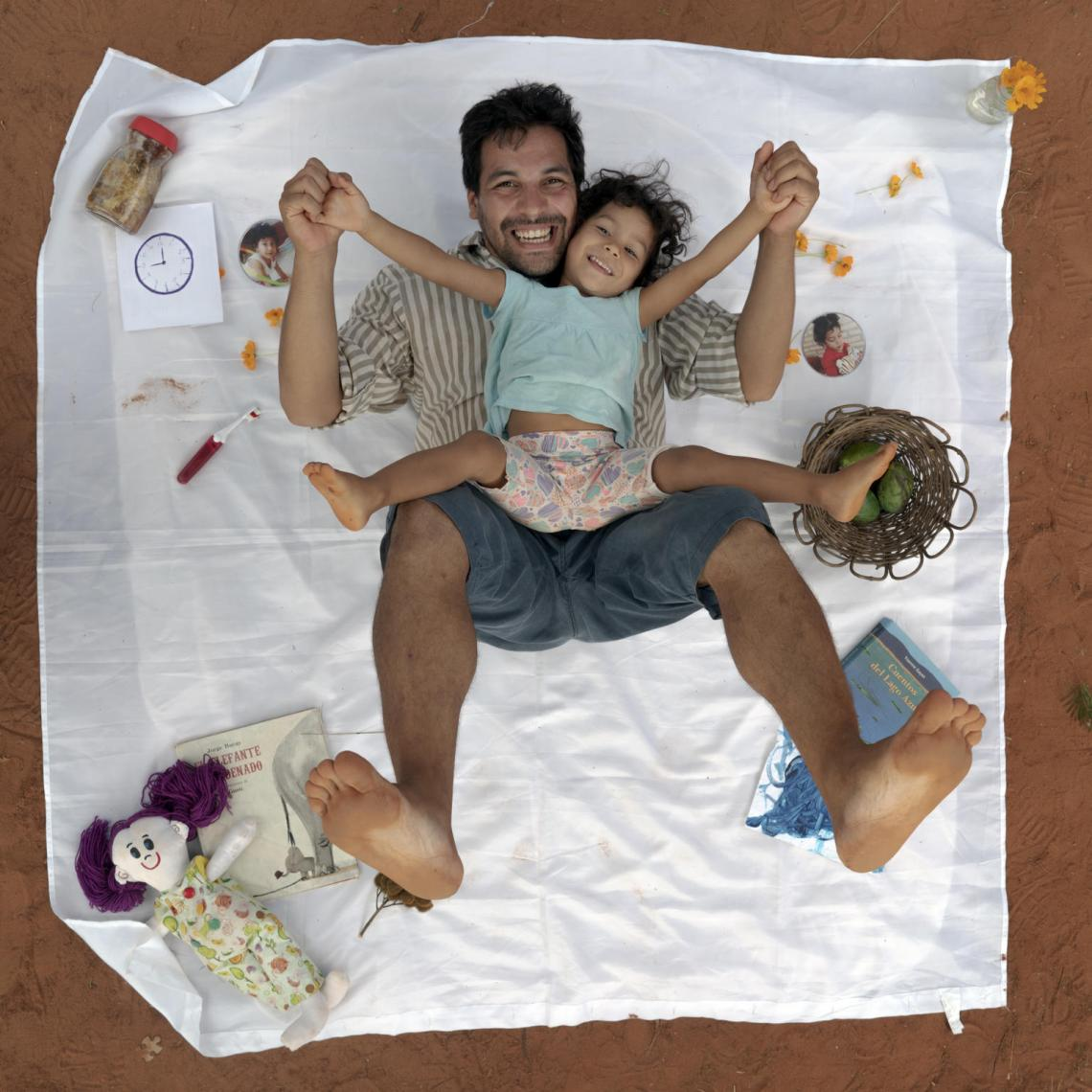 Rafael and Selva pose for a portrait with items that represent the family's change in lifestyle.
