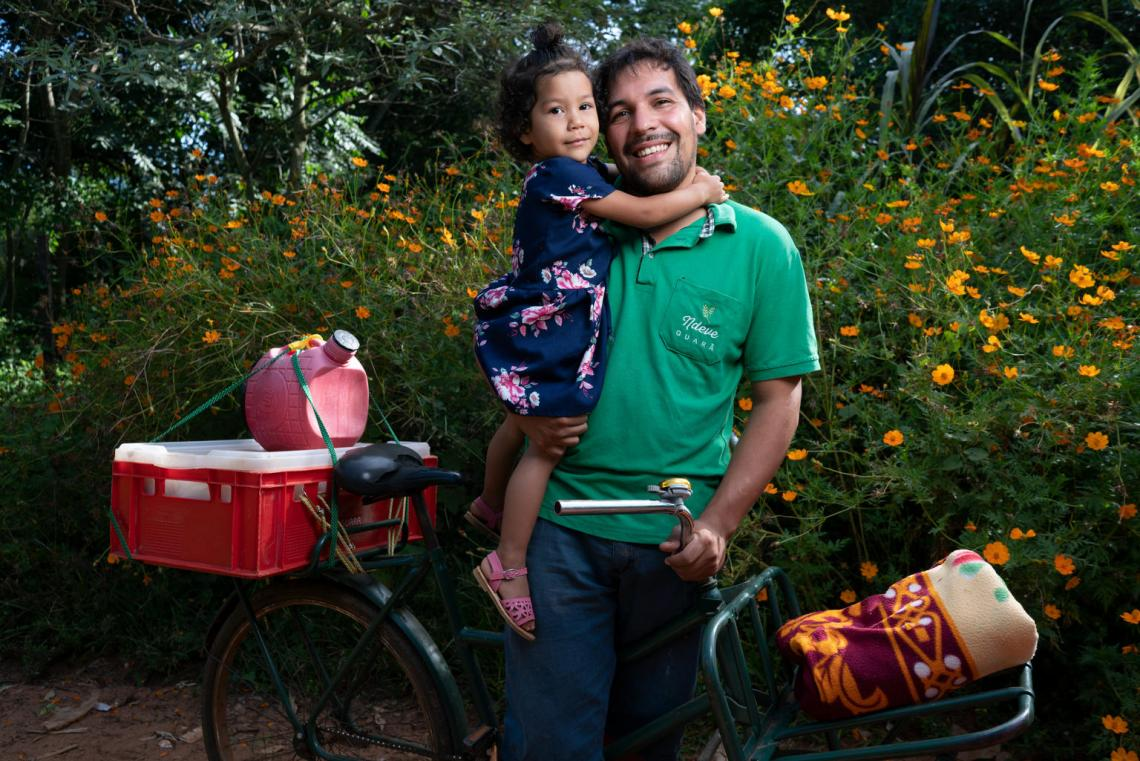 Rafael Alfonso Araujo, 27, holds his daughter Selva, 2, outside their home in Areguá , Paraguay, where Rafael and his wife Luma, 28, run an independent bakery.