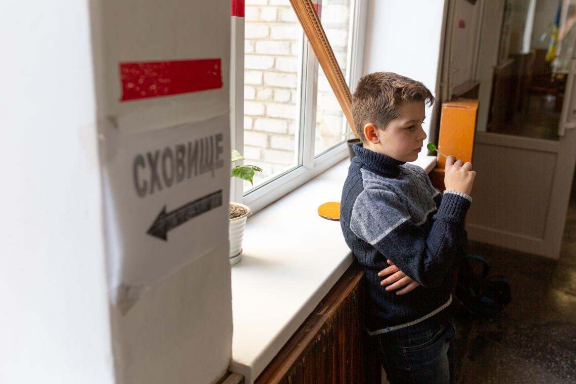 Ukraine. A child stands near a window at a school.