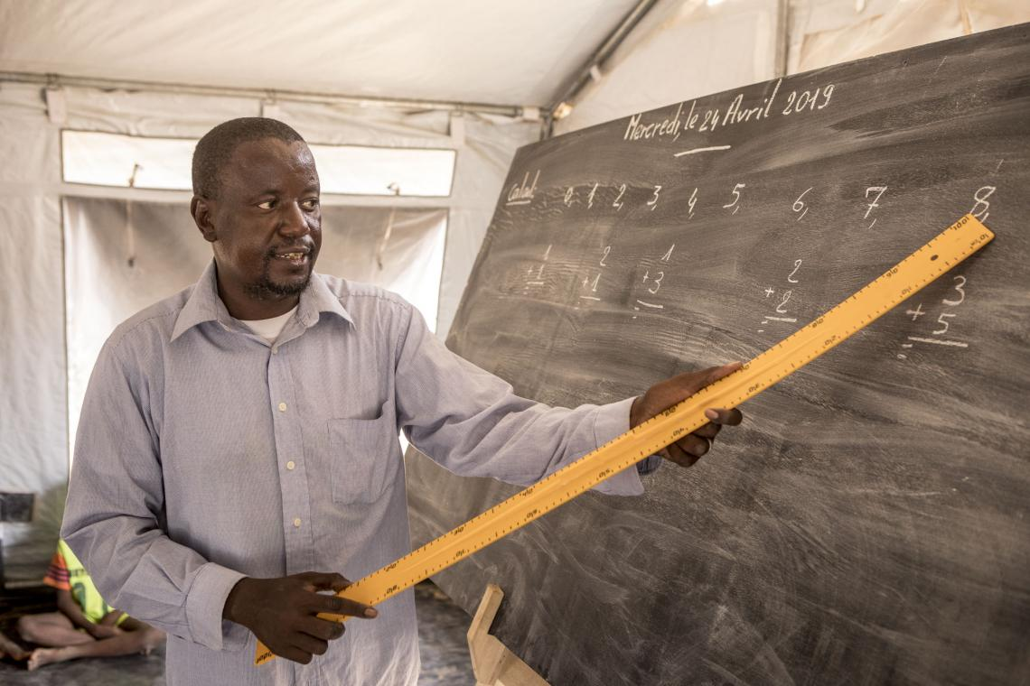 Mali. A teacher stands by a blackboard in a temporary learning centre,
