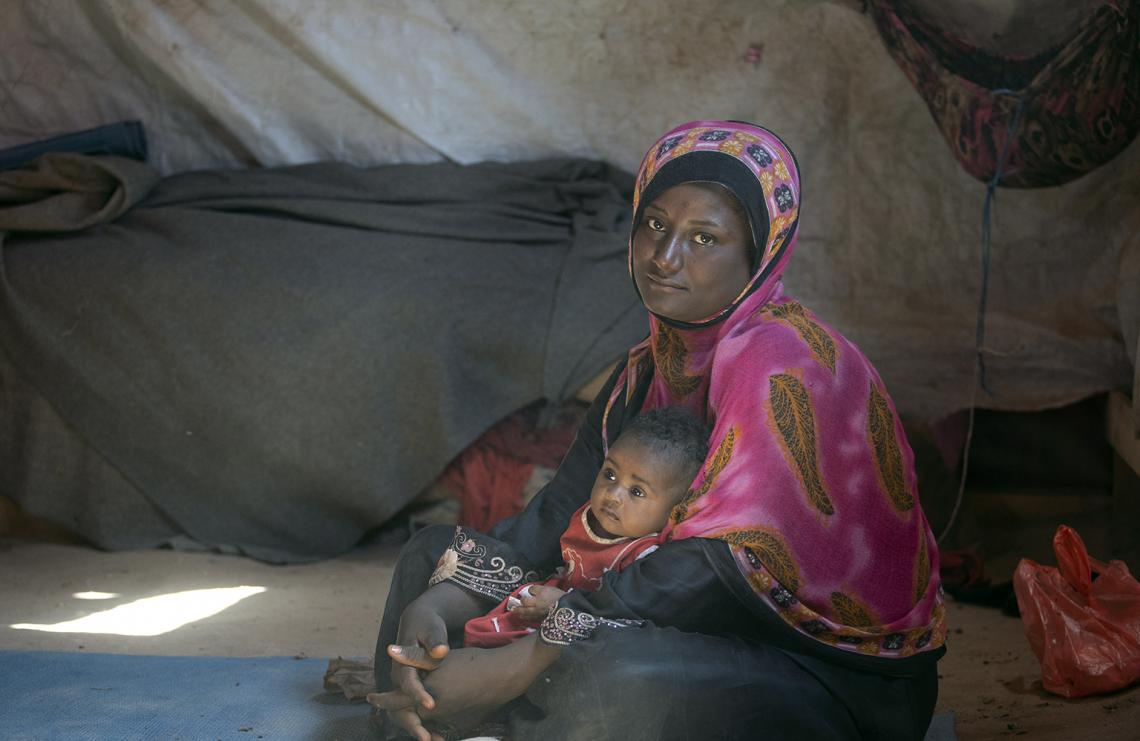 Yemen. A woman sits with her daughter inside a tent for internally-displaced persons in Lahj governorate, southern Yemen.