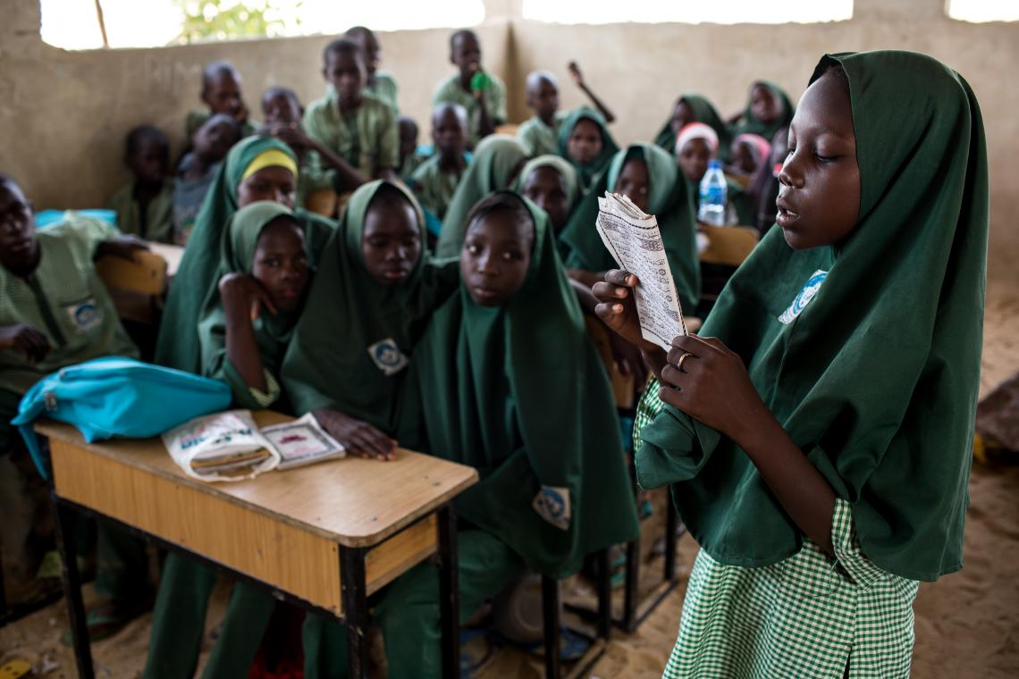 Nigeria. A girl reads to classmates in Borno state.