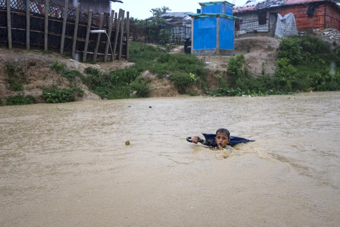 Bangladesh. A young boy navigates a river near the Cox's Bazar camp in Bangladesh that is swollen from days of monsoon rain as he collects plastic bottles, which he sells for money to help his family purchase vegetables and fish to eat.