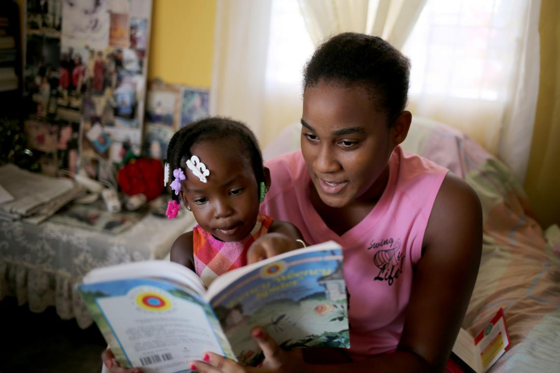 A young girl and a teenage girl read a book together in Belize.