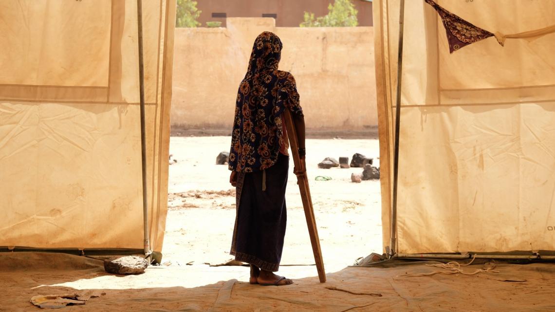 Mali.  Una niña desplazada se apoya en una muleta fuera de una tienda.