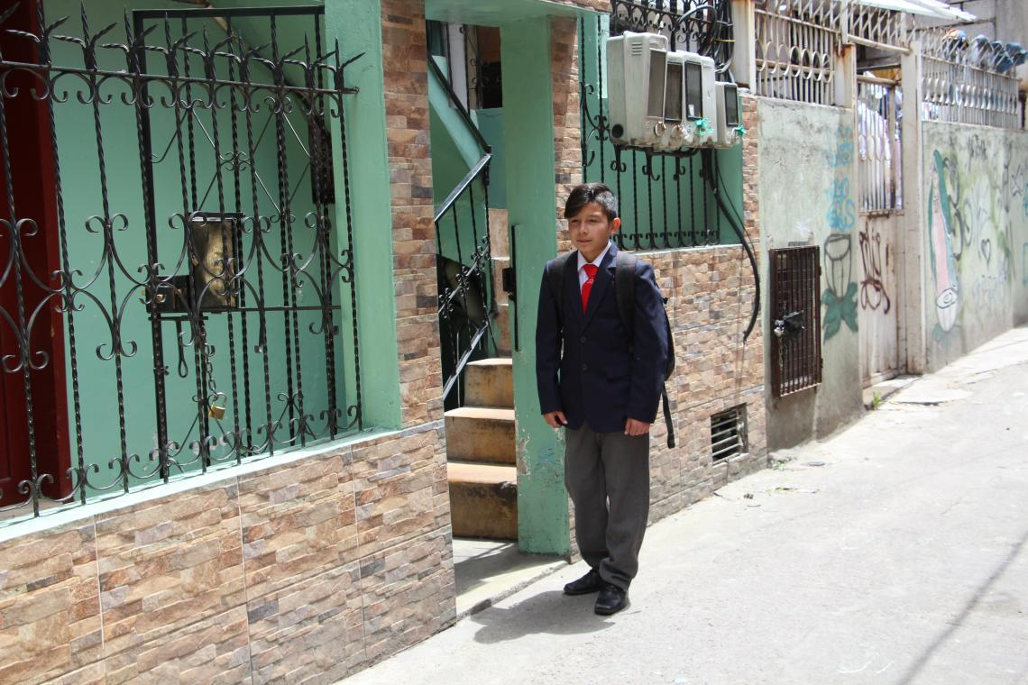 Ecuador. A boy stands outside his home wearing his school uniform.
