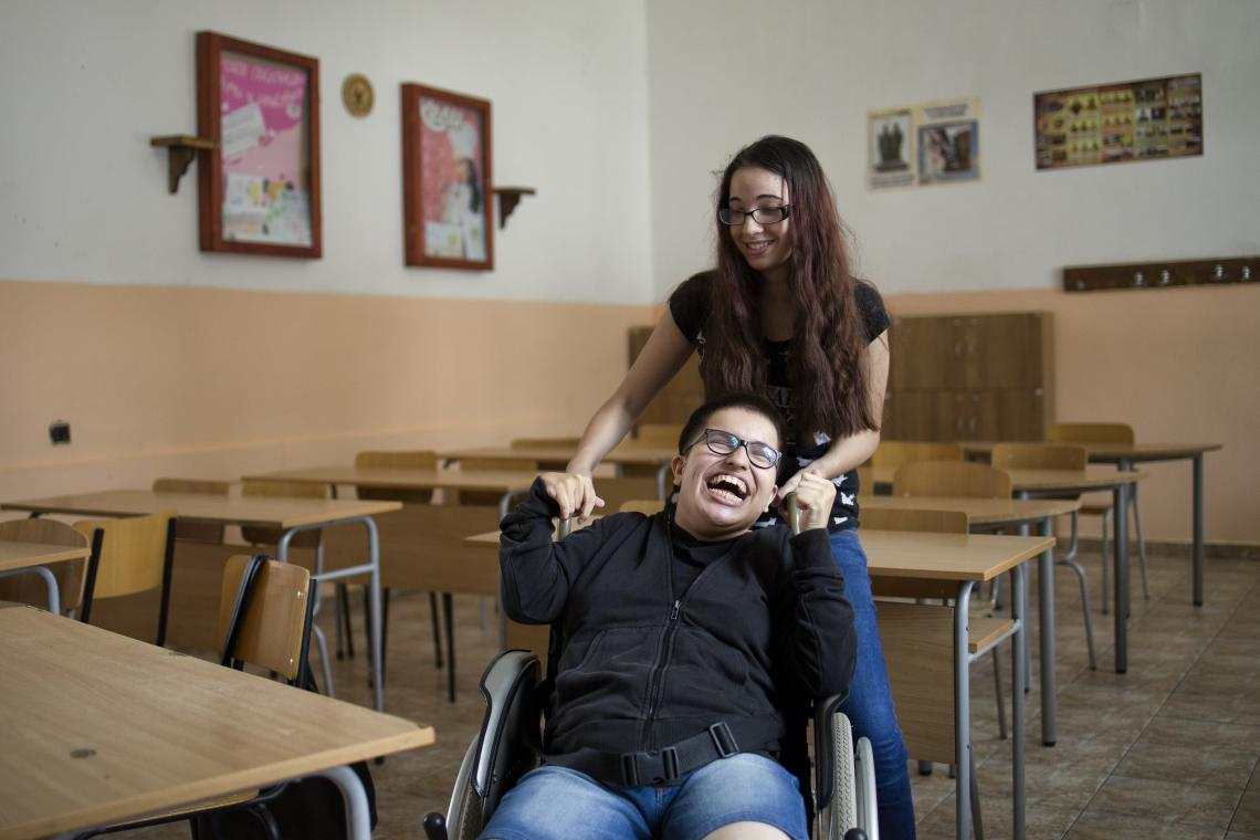 Bulgaria. A teenager living with cerebral palsy laughs with a friend.