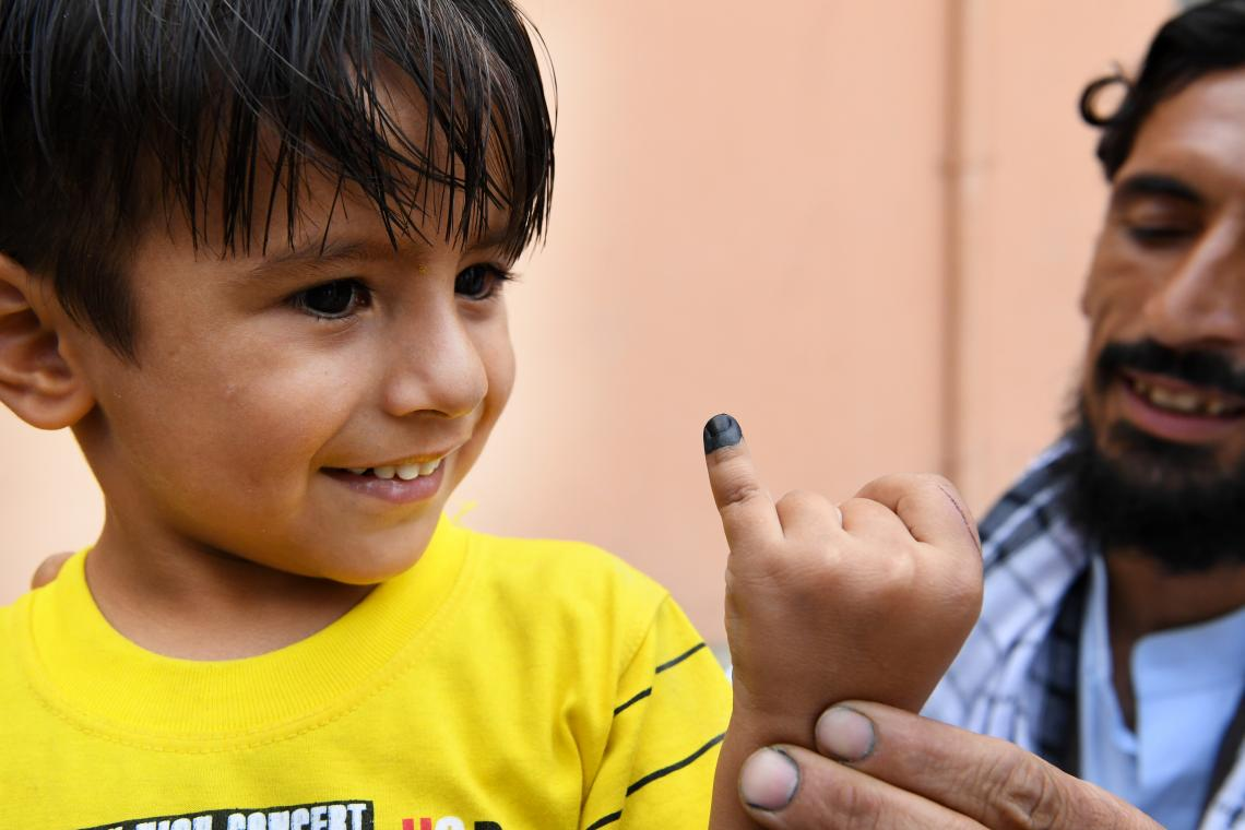 A boy raises a finger marked by a polio vaccinator, Afghanistan