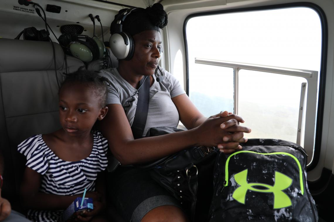 A woman and a child are evacuated after hurricane Dorian