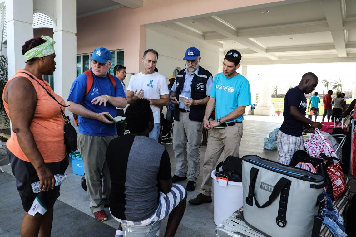 A UNICEF worker talks to families affected by the hurricane.