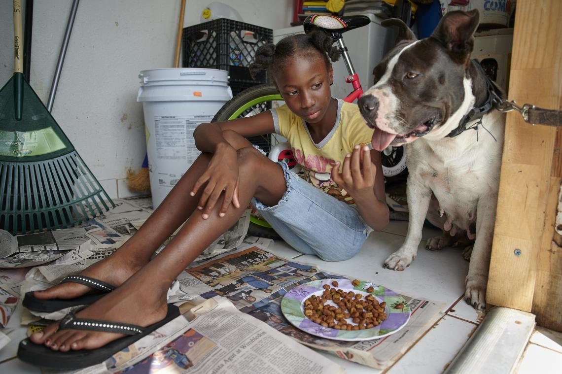 A girl feeds her dog