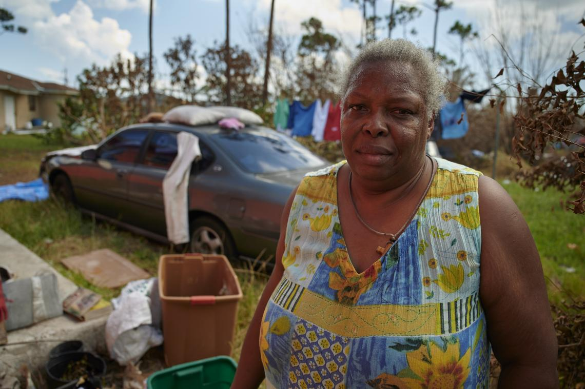 A owemab cleans up her yard outside her house after the hurricane.