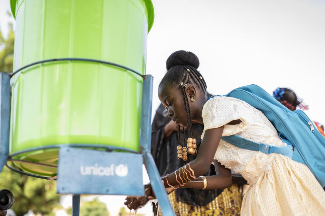 A ten-year-old girl in Niger washes her hands at an outdoor pump.